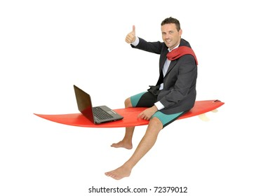 Young businessman laying in a surf board with laptop