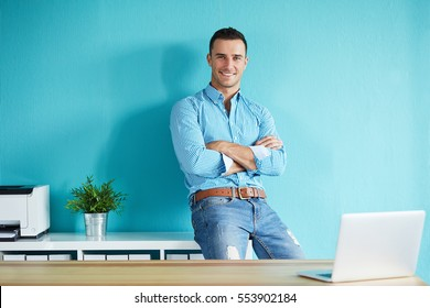 Young businessman leaning against a shelf in the office