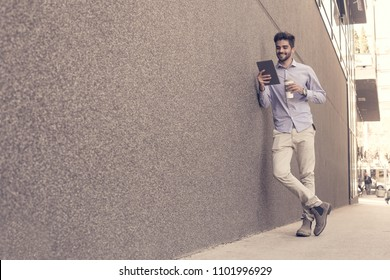Young businessman leaning against wall with digital tablet. Man holding cup of coffee.