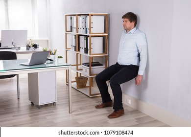 Young Businessman Leaning On Wall Doing Workout At Workplace