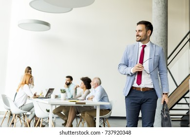 Young businessman leaves a meeting while other business people stay in office