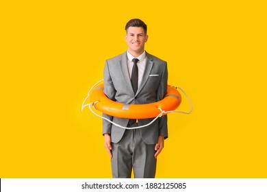 Young businessman with lifebuoy on color background