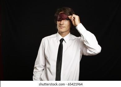 young businessman looking below sleep mask
