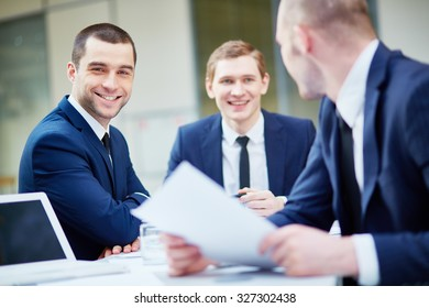 Young businessman looking at camera with his colleagues working near by