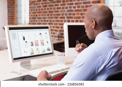 Young businessman looking at computer monitor in office