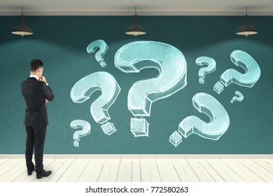 Young businessman looking at concrete wall with drawn question marks. Confusion and faq concept. 3D Rendering