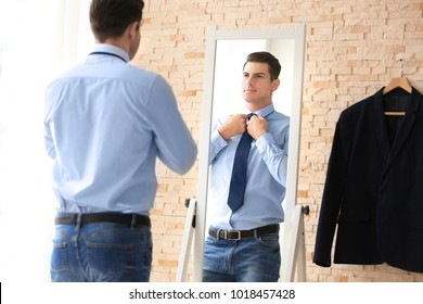 Young businessman looking at himself in mirror indoors