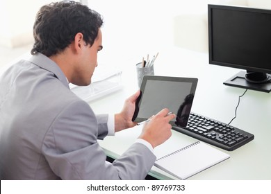Young businessman looking at his tablet in his office