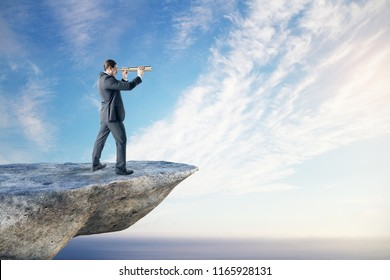 Young businessman looking into the distance on cliff. Bright sky background. Research and occupation concept