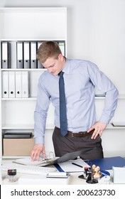 Young businessman is looking into an opened file while standing in front of a shelf in the office.