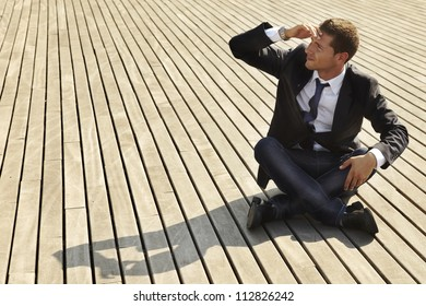 young businessman looking for job. He is sitting on wooden floor and wraps up  his face with the hand