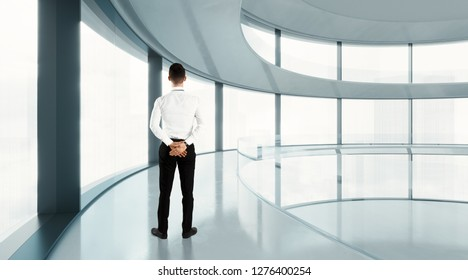 Young businessman looking megalopolis through window being in office of future