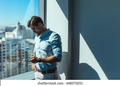 Young businessman looking at mobile phone standing beside a window. Man dressed in formals standing near window of highrise office building overlooking the cityscape.