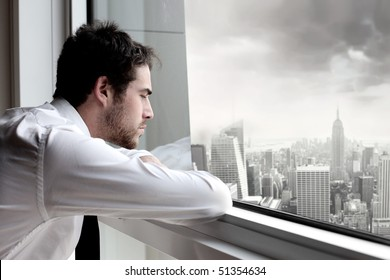Young businessman looking out of a window