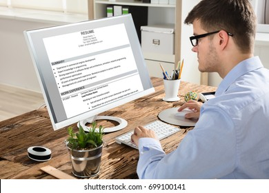 Young Businessman Looking At Resume On Computer Screen At Workplace