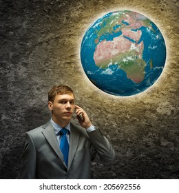 Young businessman looking thoughtfully at Earth plane. Elements of this image are furnished by NASA
