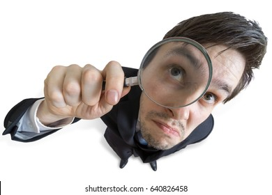 Young businessman is looking through magnifying glass. Isolated on white background. View from above.