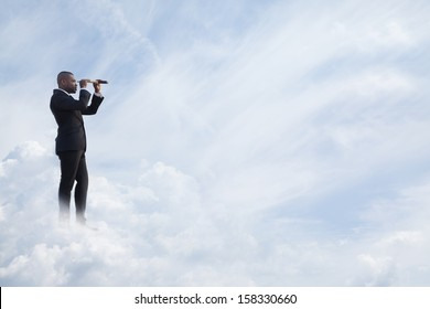 Young businessman looking through telescope in the sky