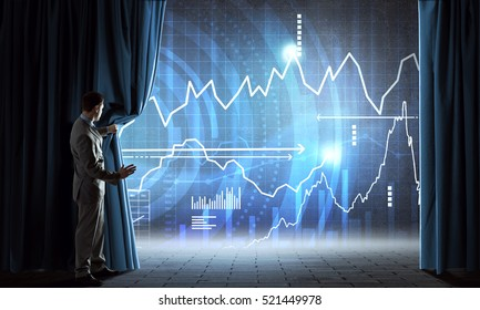 Young businessman looks at graphs and diagrams behind curtain