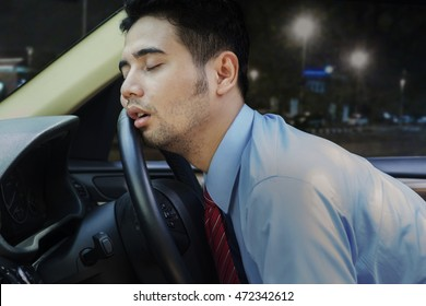 Young businessman looks tired and sleeping inside a car on the steering wheel