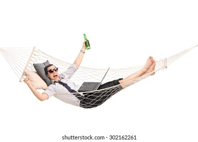 Young businessman lying in a hammock with a beer in his hand and working on a laptop isolated on white background