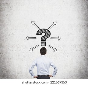 Young businessman making a decision. Arrows and question mark above his head.