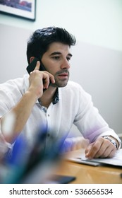 Young businessman making a phone call at his office.