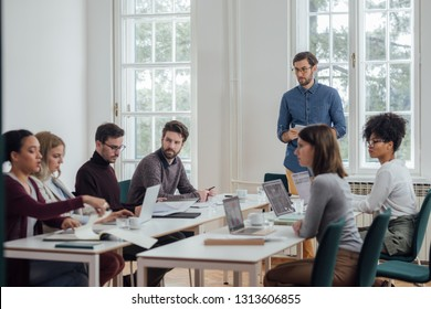 Young businessman making a presentation to his colleagues at the modern office space.