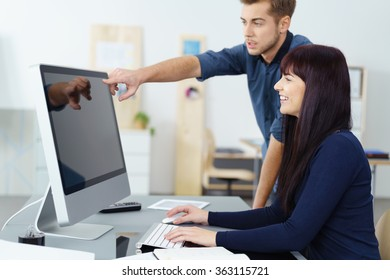 Young businessman in a meeting with a female colleague pointing to a large desktop monitor as she smiles with satisfaction at the information, profile view