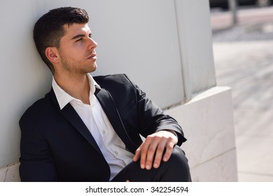 Young businessman near a modern office building wearing black suit and white shirt sitting on the floor. Man with blue eyes in urban background