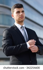 Young businessman near a modern office building wearing black suit and tie. Man with blue eyes