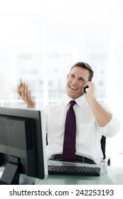 Young businessman negotiating on the phone at workplace