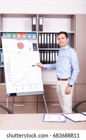 Young businessman next to a flip chart in an office. Finance and business.