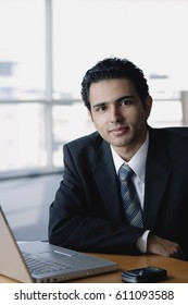 Young businessman next to laptop, looking at camera