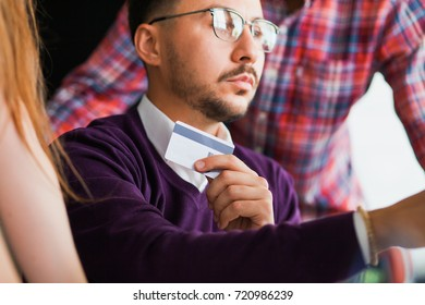 Young businessman at office credit card online commerce looking at computer monitor. Casual look, internet shopping