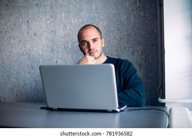 Young businessman in office, looking at camera and smiling.