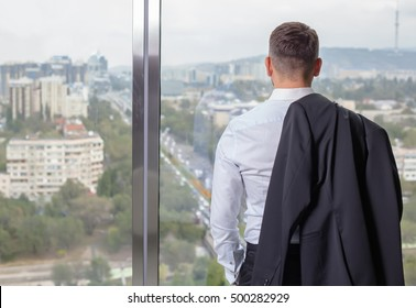 Young businessman at office on the top floor at the front of the window to standing back. with panoramic views of the city