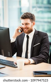 Young businessman at the office sitting at his desk and talking on a phone