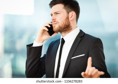 Young businessman at the office sitting at his desk and thinks about the work problem and busy talking on a phone