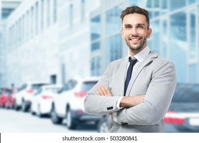 Young businessman on blurred car salon background. Car sale and rent concept.