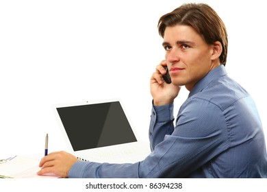 Young businessman on cellphone sitting in front of laptop isolated on white background