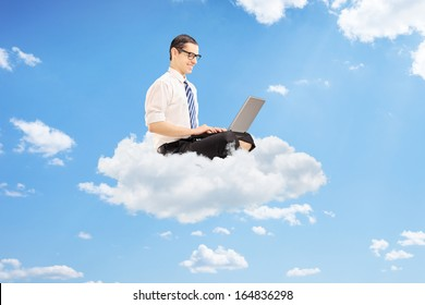 Young businessman on clouds working on a laptop, against sky