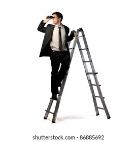 Young businessman on a ladder using binoculars