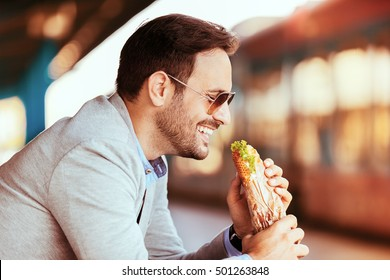 Young businessman on railroad station is eating sandwich.