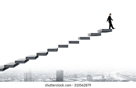 Young businessman on staircase top representing success concept