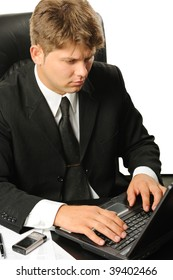 The young businessman on a workplace. It is isolated on a white background