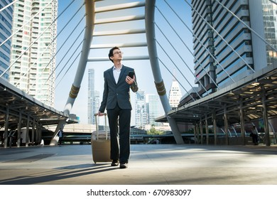 Young Businessman one hand carrying travel suitcase another hand using mobile phone application for finding directions and looking up, future job, hope, direction,  way and  opportunity concepts.