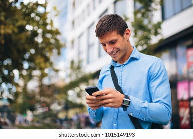 Young businessman online via smartphone in the city
