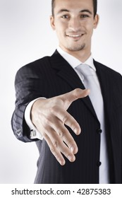 young businessman open his hand for a handshake. Focused on the hand. (Hand retouched in detail)