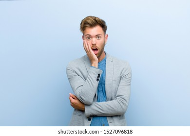 young businessman open-mouthed in shock and disbelief, with hand on cheek and arm crossed, feeling stupefied and amazed against blue background